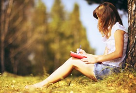 Girl writing in her journal under a tree on a summers day